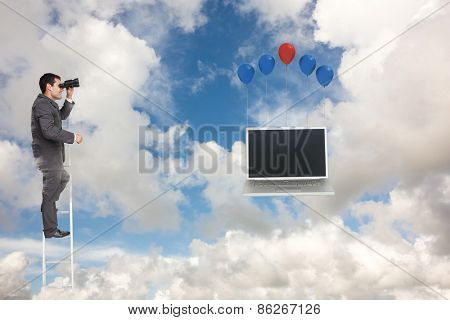 Businessman standing on ladder against blue sky with white clouds