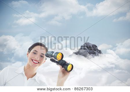 Smiling business woman with binoculars against mountain peak through the clouds