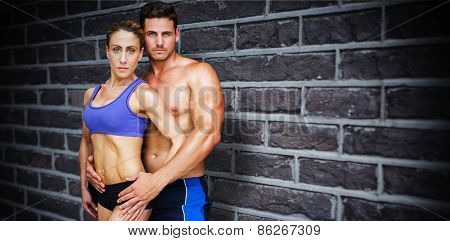 Bodybuilding couple against red brick wall