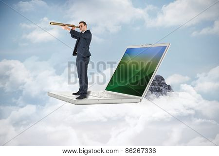 Businessman looking through telescope against mountain peak through the clouds