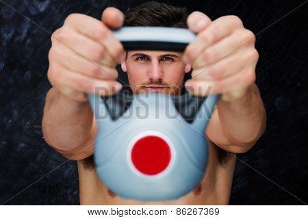 Bodybuilder holding kettlebell against black background