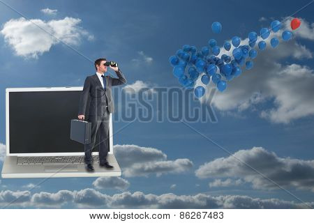 Businessman looking through binoculars against sky and clouds
