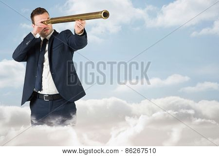 Businessman looking through telescope against cloudy sky