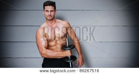 Bodybuilder lifting dumbbell against painted blue wooden planks
