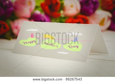mothers day greeting against tulips with card