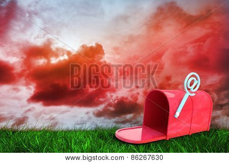 Red email post box against green grass under red cloudy sky
