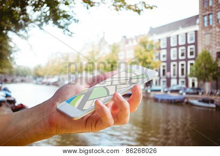 Man using map app on phone against canal in amsterdam