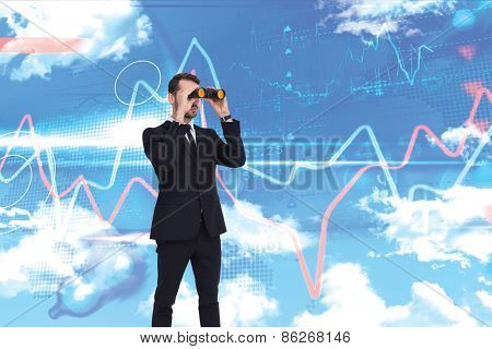 Elegant businessman standing and using binoculars against blue sky