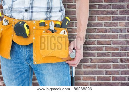Technician with tool belt around waist against red brick wall