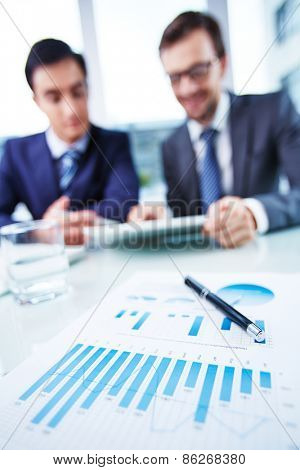 Business document at workplace and two businessmen working with touchpad on background