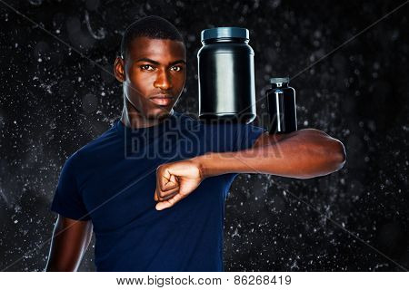 Fit man holding bottles with supplements on his biceps against black background