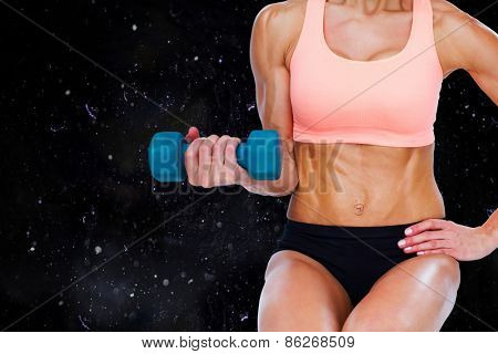Strong woman doing bicep curl with blue dumbbell against black background