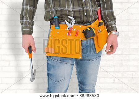 Manual worker holding hammer against white wall