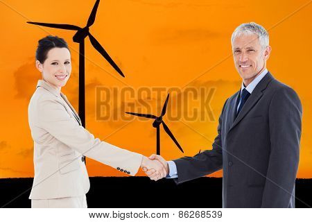Smiling business people shaking hands while looking at the camera against wind turbines with a sunset