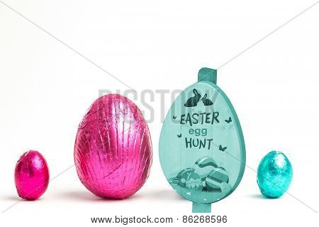Easter egg hunt sign against two large easter eggs between two small ones