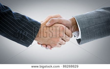 Business people shaking hands against grey vignette