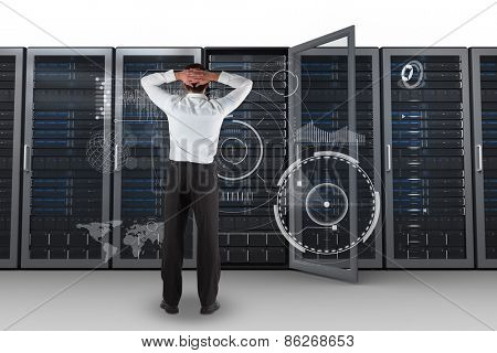 Businessman standing back to the camera with hands on head against server towers