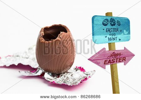 Easter egg hunt sign against easter egg unwrapped in pink foil with bite taken out