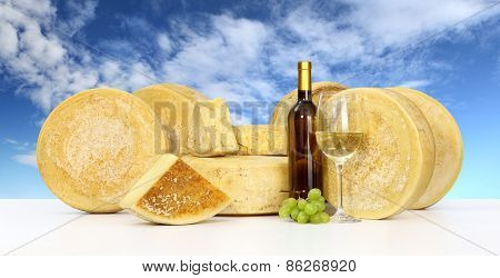 various forms of cheese wine glass bottle sky background