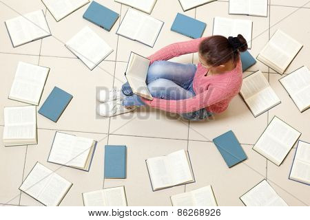 Girl reading a book, top view. Blurred text is unreadable