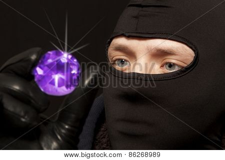 Thief. Man in black mask with a big emerald. Focus on thief