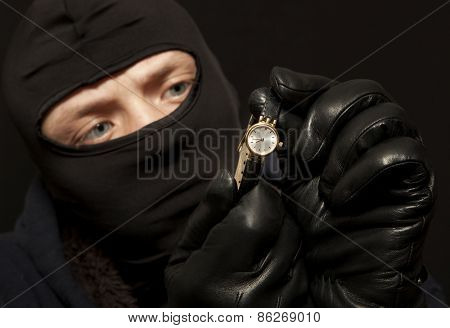 Thief. Man in black mask with a golden watch. Focus on golden watch