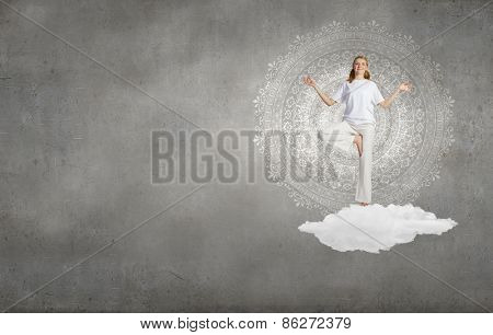 Young smiling girl standing on cloud and meditating