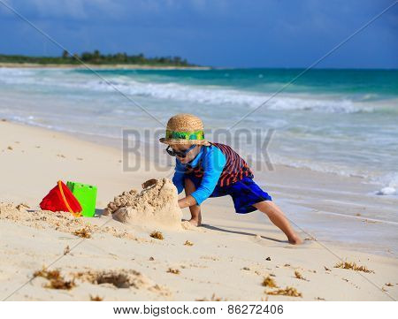 little boy building sandcastle on the beach