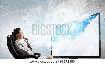 Young businesswoman in chair near tv screen