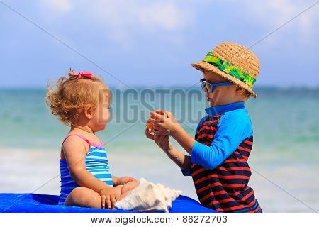 cute infant girl and little boy playing with shells on the beach