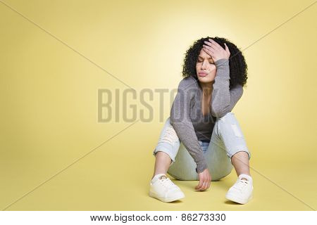 Unlucky woman being sad about failure, isolated on yellow background with empty copy space.