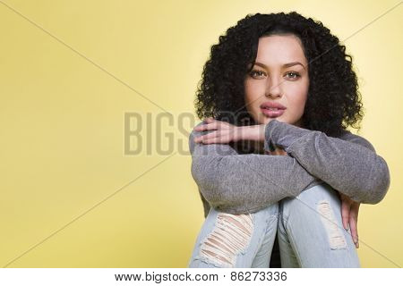 Charming girl with sexy look isolated on yellow background with copy space.