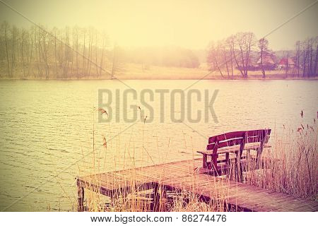Vintage Stylized Photo Of Bench At The Lake.