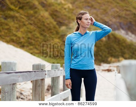 Sporty young woman standing not far from the beach