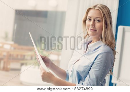 Businessowman standing next to window with papers