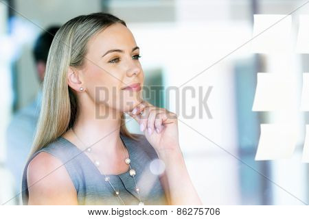 Young businesswoman standing and looking at notes