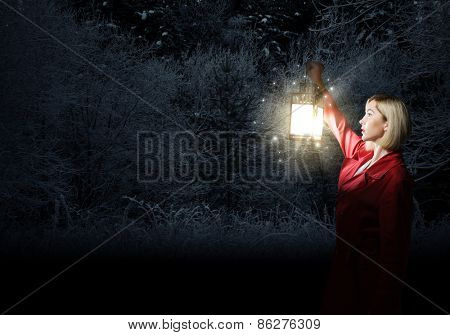Young blonde in red cloak with lantern in night forest
