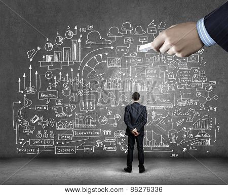 Rear view of businessman looking at business sketch on wall