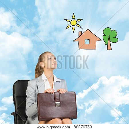 Business woman in skirt, blouse and jacket, sitting on chair, holding briefcase imagines house with