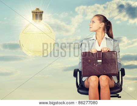 Business woman in skirt, blouse and jacket, sitting on chair, holding briefcase imagines perfume. Ag