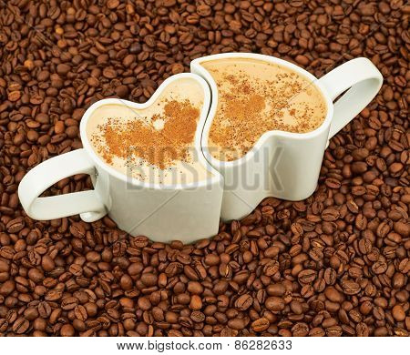 Two cups on coffee beans