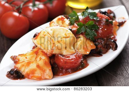 Italian tortellini pasta with tomato and olive sauce