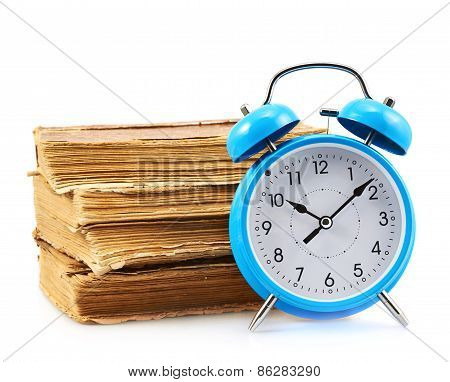 Blue alarm clock next to a stack of books