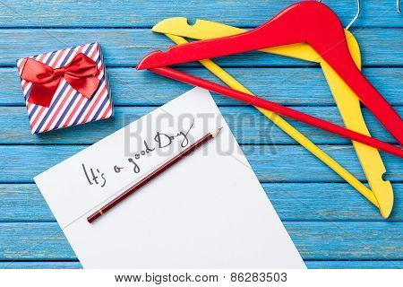 Pencil And Paper With Inscription Near Hangers And Gift Box