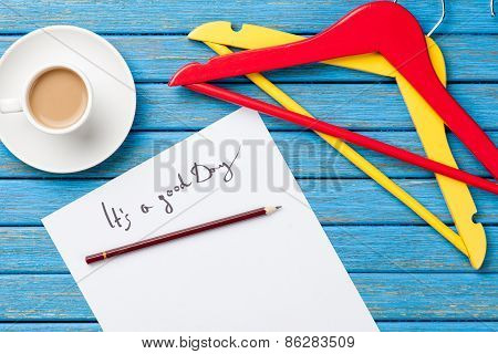 Hangers And Cup Of Coffee Near Paper With Inscription