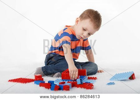 Little Boy Playing With Designer On The Floor