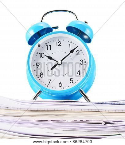 Alarm clock over the pile of papers