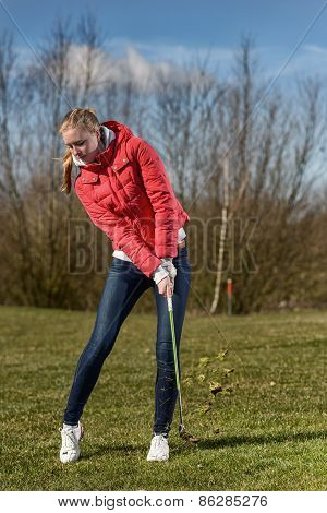 Female Golfer Striking In The Rough