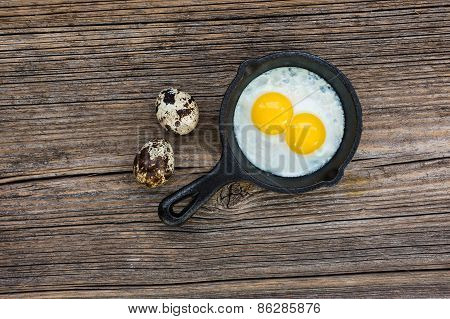 Fried quail eggs in pan on wooden background