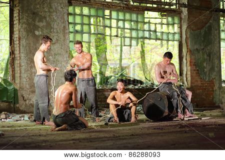 Five young guys in torn gray pants with rope in his hands in abandoned building